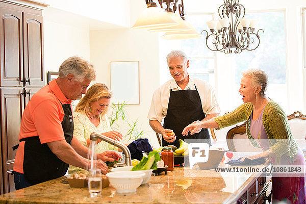Gruppe von Senioren  die in der Küche eine Mahlzeit zubereiten