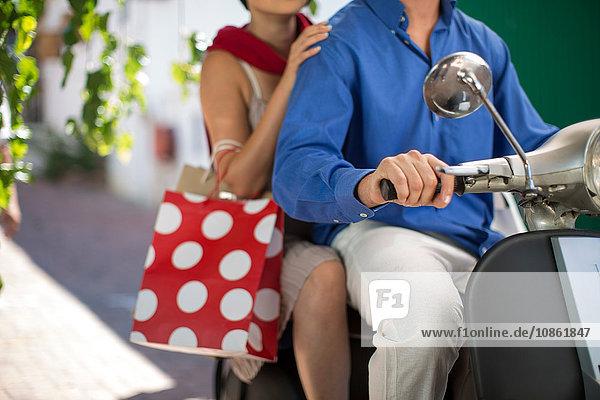 Schnappschuss eines jungen Paares mit Einkaufstaschen auf einem Moped in der Stadt