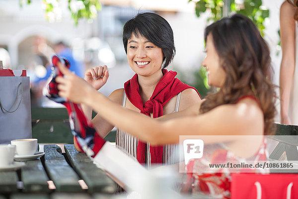 Frau zeigt Freundin neues Kleid im städtischen Straßencafé