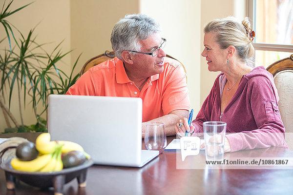 Älteres Ehepaar benutzt Laptop und chattet am Schreibtisch