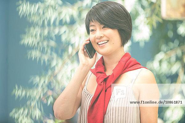 Junge Frau chattet auf Smartphone in der Stadt
