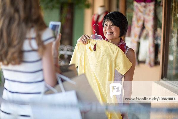 Zwei junge Frauen fotografieren Kleid mit Smartphone in der Stadt