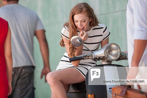 Junge Frau sitzt auf Moped und trägt Lippenstift in der Stadt auf