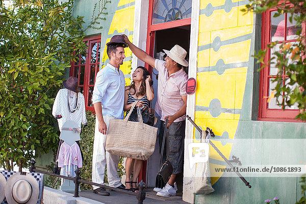 Ladenbesitzer probiert Hut auf Einkaufspaar in der Stadt