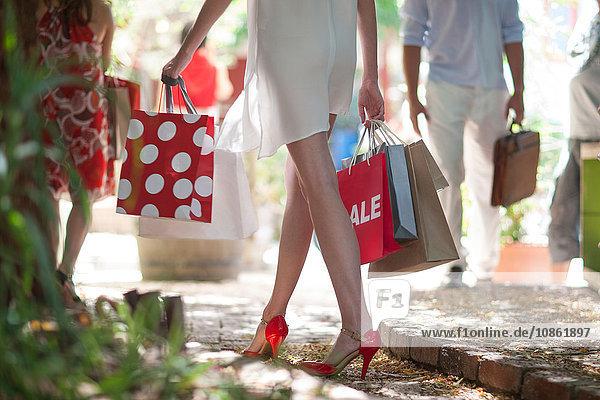 Hüftuntere Ansicht einer jungen Frau  die mit Einkaufstaschen durch die belebte Stadtstraße schlendert