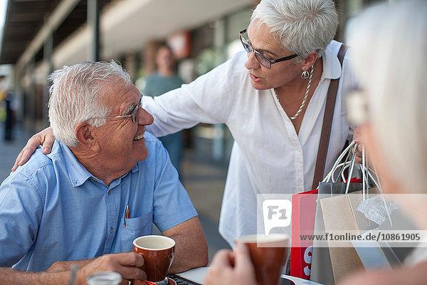 Shopperin begrüßt älteren Mann im Straßencafé