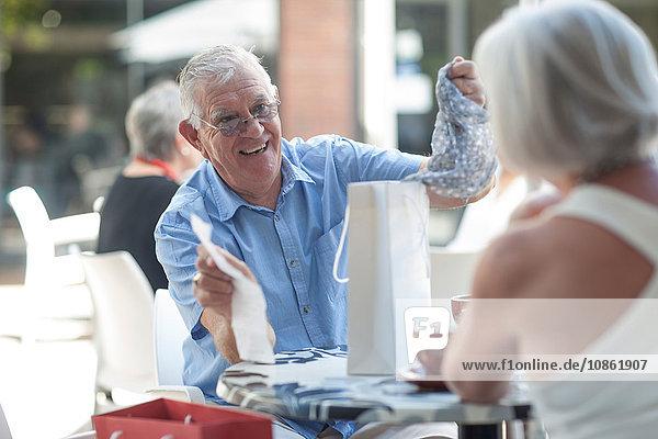 Älterer Mann entfernt Schal aus Einkaufstasche für Frau im Straßencafé