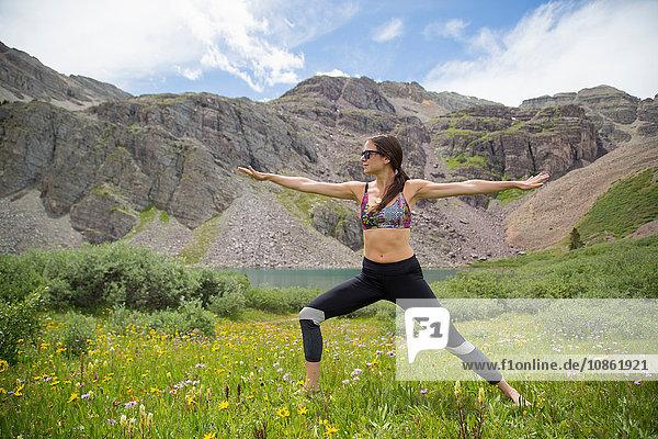 Frau praktiziert Yoga auf einer Wiese  Kathedralensee  Aspen  Colorado