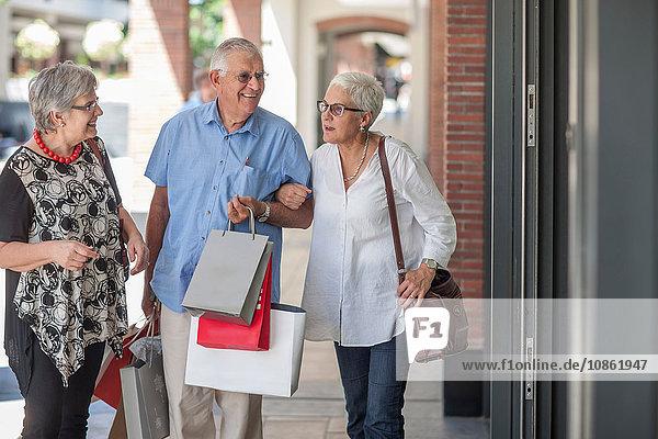 Drei reife Freunde gehen die Straße entlang  älterer Mann trägt Einkaufstüten
