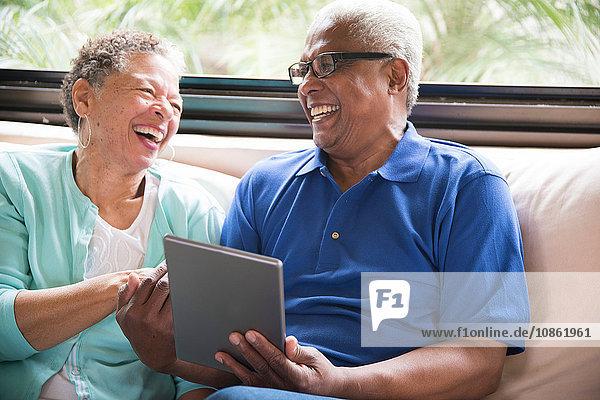 Älteres Ehepaar sitzt auf dem Sofa und benutzt ein digitales Tablett