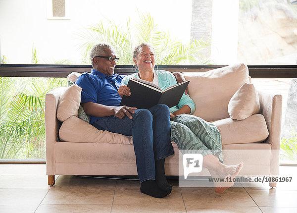 Älteres Ehepaar sitzt auf dem Sofa und blättert im Fotoalbum