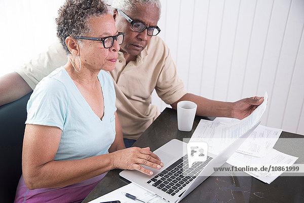Älteres Ehepaar sitzt am Tisch  benutzt Laptop und sieht sich Papierkram an