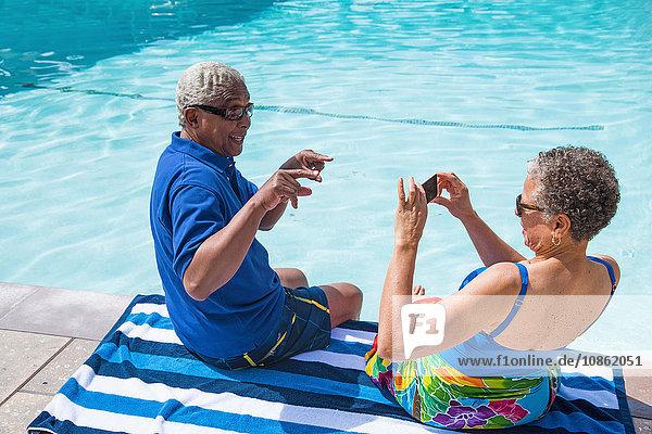 Älteres Ehepaar sitzt am Swimmingpool  Frau fotografiert Mann mit Smartphone
