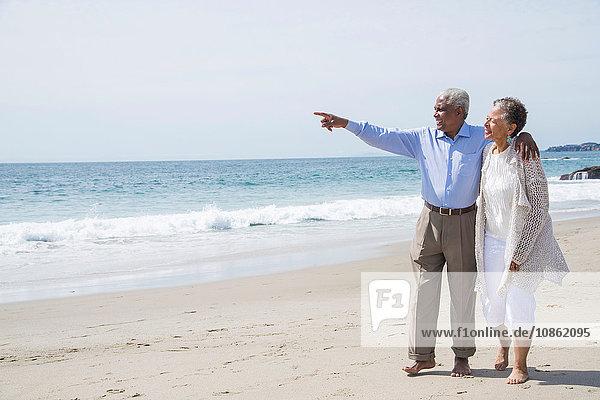 Älteres Ehepaar wacht gemeinsam am Strand auf und betrachtet die Aussicht