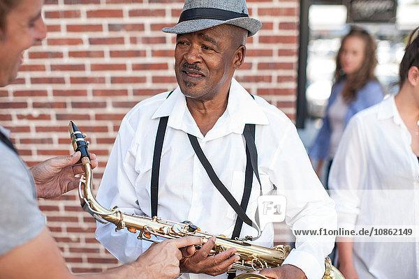 Straßenmusikant im Gespräch mit Passanten