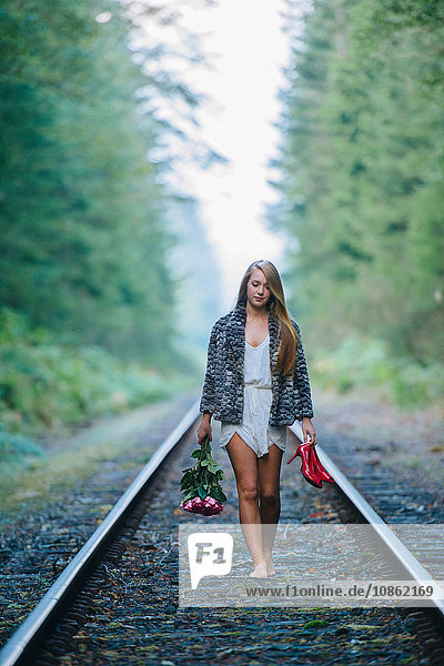 Teenage girl  walking along train track  holding red shoes and flowers