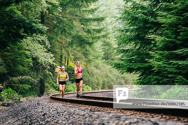 Young woman and teenage girl running along rural train track