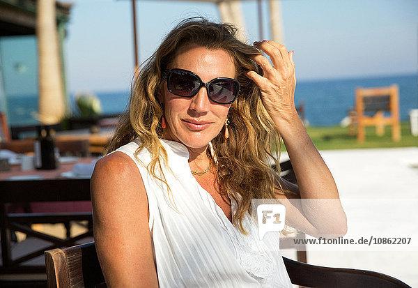 Porträt einer reifen Frau mit Sonnenbrille im Küstencafé  Spanien