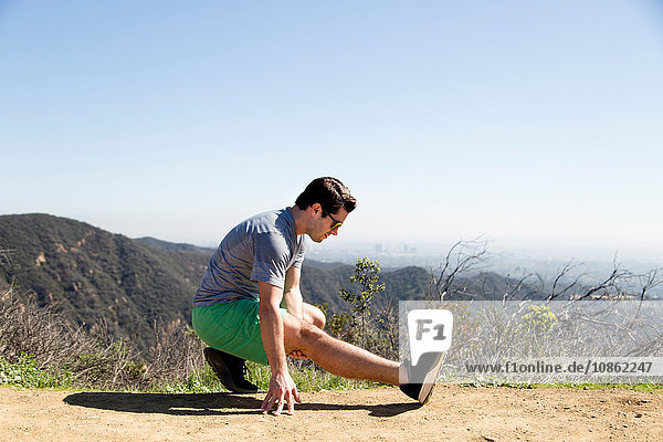 Mann kauert auf Berg und macht Beindehnungsübung