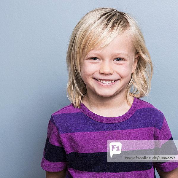 Porträt eines blondhaarigen Jungen  der lächelnd in die Kamera schaut