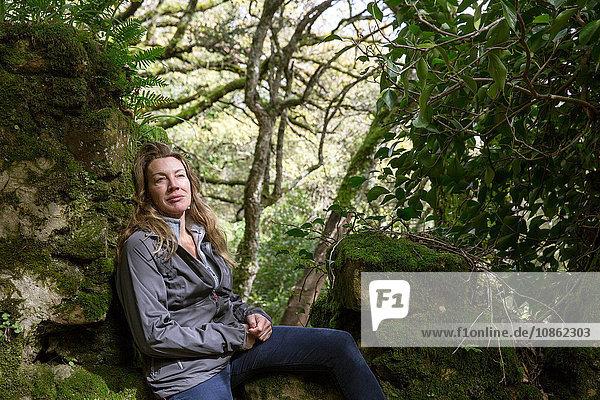 Weibliche Wanderin auf moosbedeckten Waldfelsen sitzend  Spanien