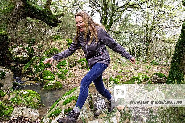 Wanderin beim Überwinden von Waldfelsen  Spanien