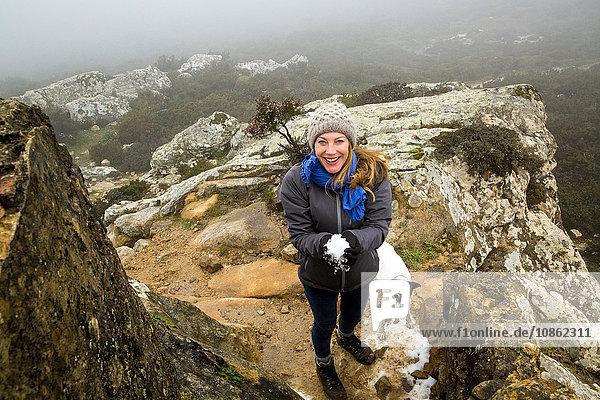 Porträt einer Wanderin mit ihrem Hund  die in nebligen Bergen einen Schneeball hält  Spanien