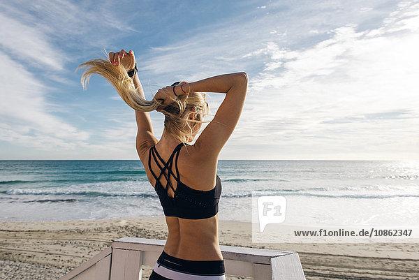 Junge Frau auf Rettungsschwimmer-Plattform  Haare hochstecken  Rückansicht