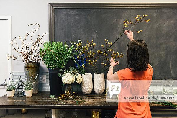 Florist arranging display in flower shop  rear view