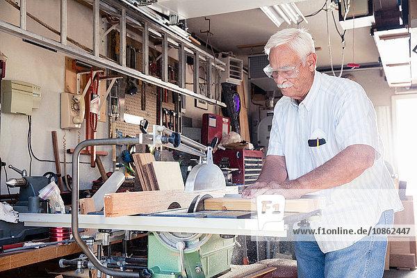 Älterer Mann sägt Holzblock auf Kreissäge in Schreinerei