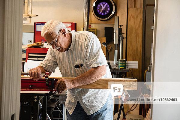 Älterer Mann platziert Holzblock auf Schreinerei-Ausrüstungswerkstatt