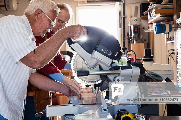 Ältere Männer sägen auf Kreissäge in Schreinerei