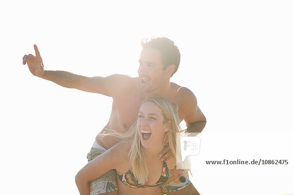 Woman giving man piggyback looking away smiling