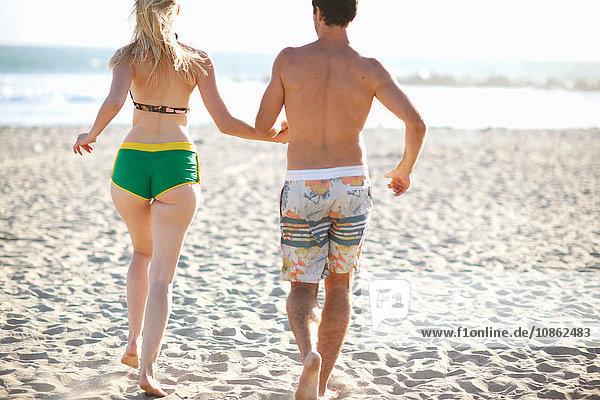 Rückansicht eines zum Meer laufenden Paares am Strand
