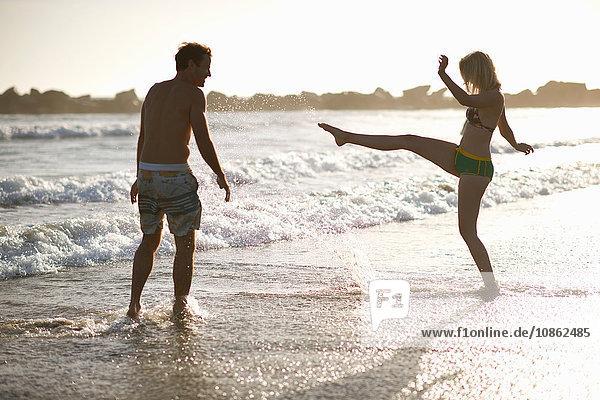 Pärchen am Strand tummelt sich im Meer