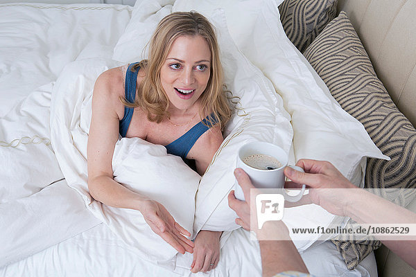 Man handing coffee to surprised woman in bed