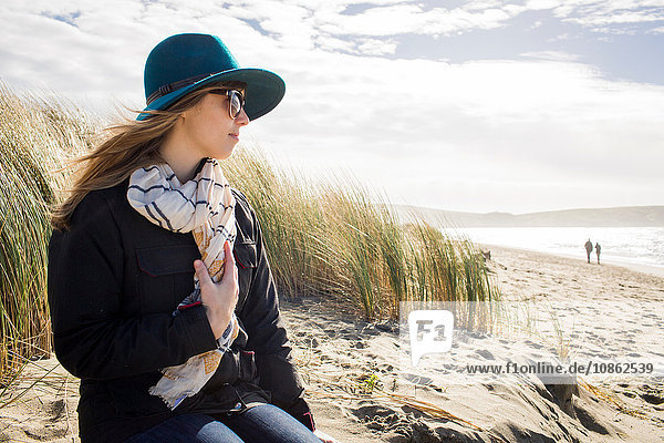 Woman wearing felt hat and sunglasses looking out from dunes  Dillon Beach  California  USA