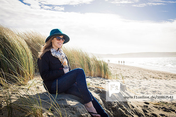 Woman wearing felt hat and sunglasses sitting on dunes,  Dillon Beach,  California,  USA
