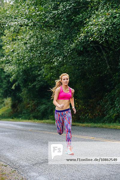 Teenage girl running up rural road