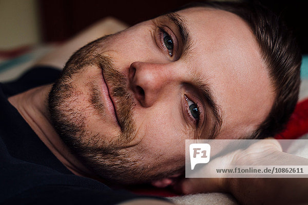 Close up portrait of handsome confident man on bed with hands behind head