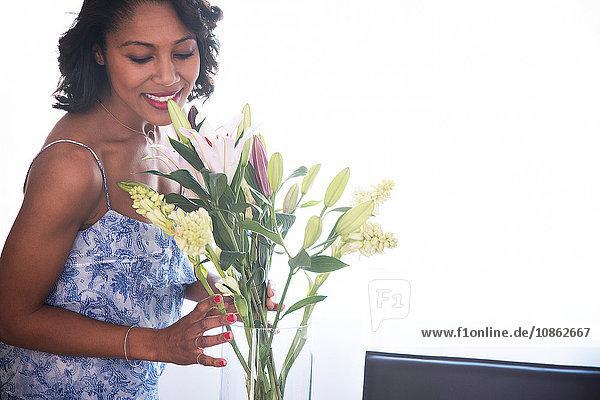 Frau arrangiert Blumen in Vase