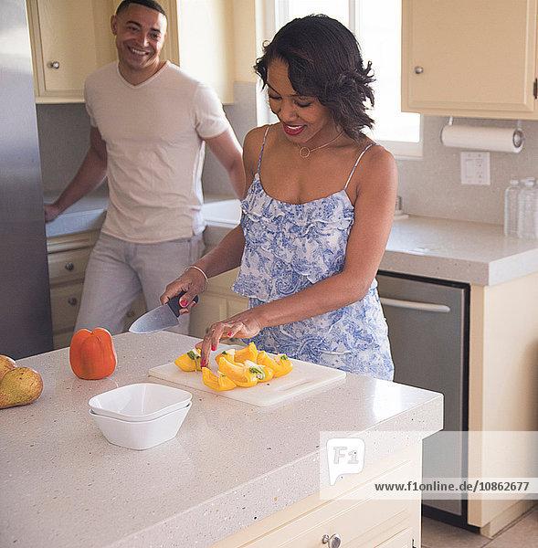 Mann unterhält sich mit Frau  die in der Küche Obst schneidet