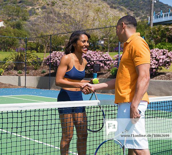 Ein Paar schüttelt sich die Hände neben dem Tennisplatznetz