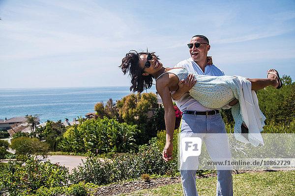 Mann trägt Frau auf einem Hügel in der Nähe des Ozeans  Los Angeles  Kalifornien