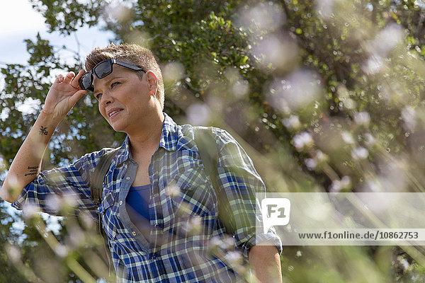 Woman hiker wearing sunglasses looking away