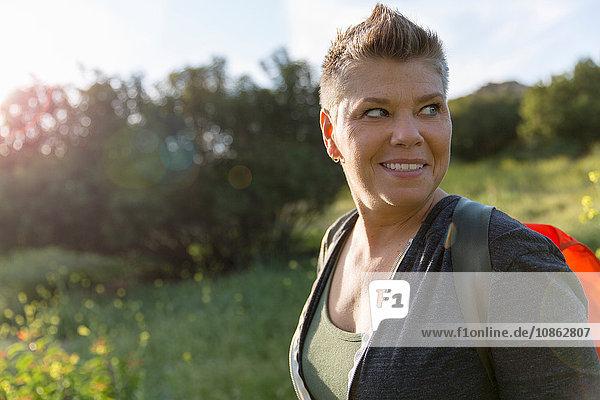 Wanderfrau schaut lächelnd über die Schulter weg