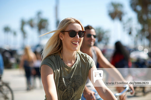 Young woman and boyfriend cycling at Venice Beach  Los Angeles  California  USA
