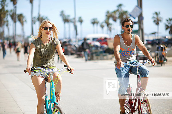 Couple cycling at Venice Beach  Los Angeles  California  USA