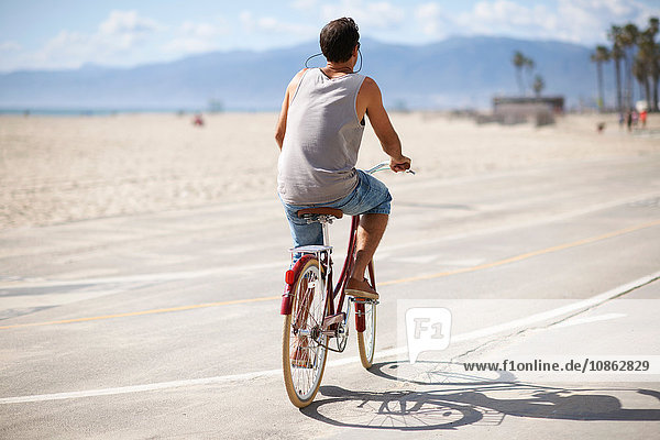 Rear view of man cycling at Venice Beach  Los Angeles  California  USA