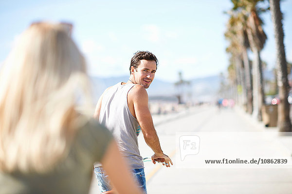Man looking back at girlfriend whilst cycling at Venice Beach  Los Angeles  California  USA